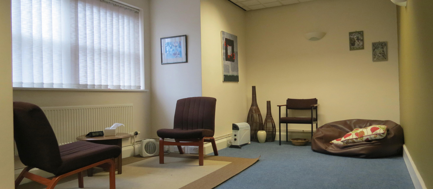 Image shows a large therapy room at Nottingham Counselling Service. There are two comfy chairs facing each other over a small coffee table in front of a window letting in natural light to the left. To the right there is another chair and a brown leat