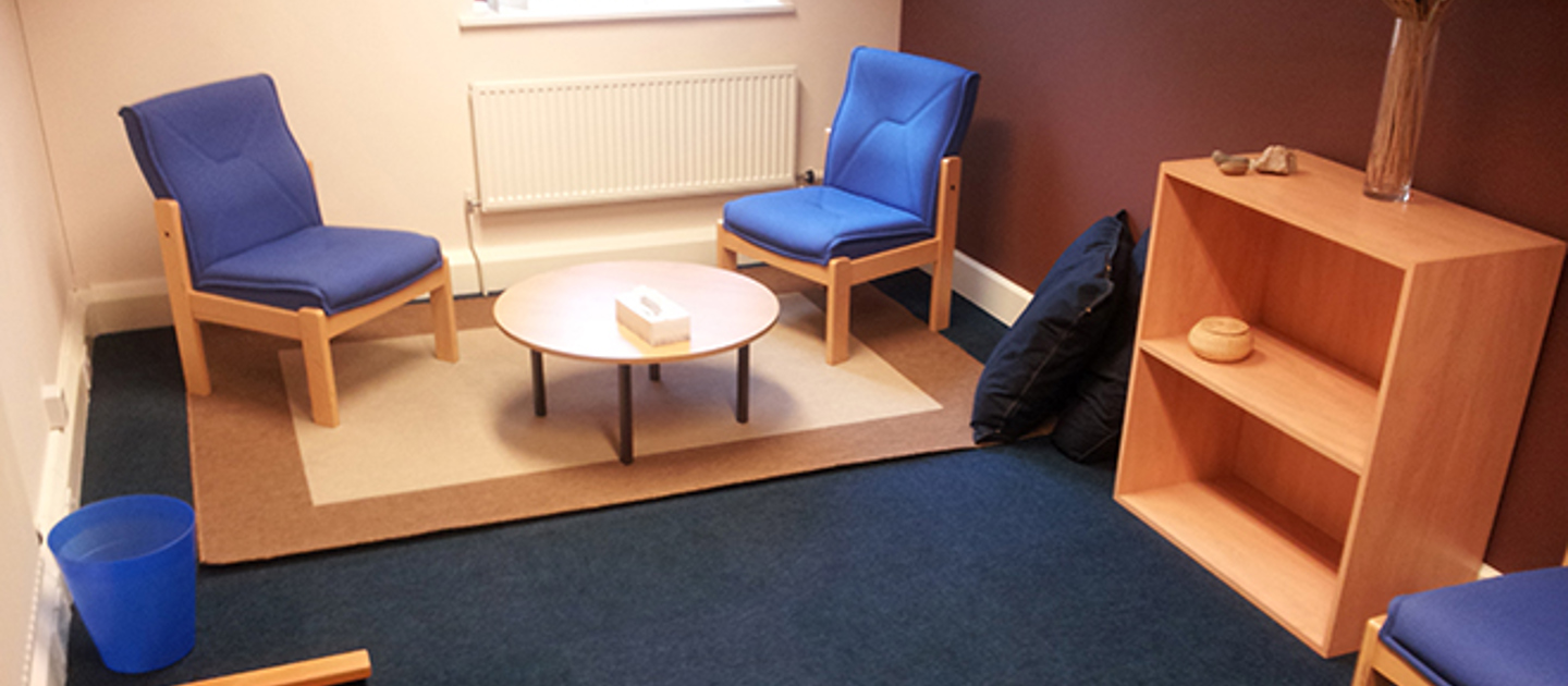 Image shows one of the therapy rooms at Nottingham Counselling Service. There are two comfortable chairs facing each other over a small coffee table. There is a bookshelf with small decorations on it to the left. There is a window in the background l